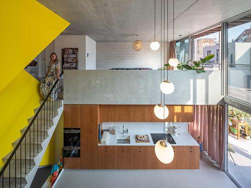 beta-three-generation-house-buiksloterham-photo-interior-kitchen-living-room-yellow-staircase-concrete-image-Ossip-van-Duivenbode